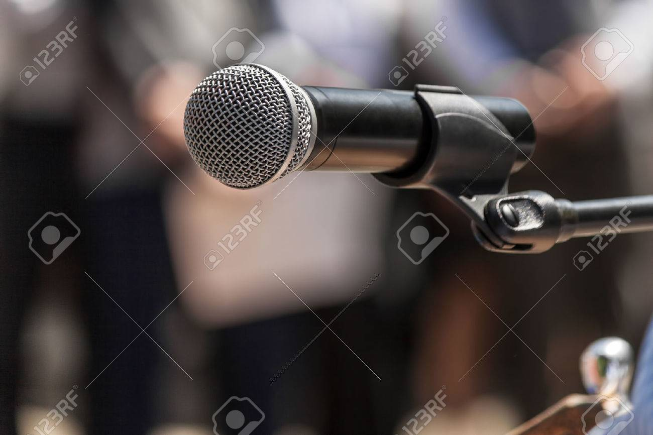 Microphone on the background blurred figures of people during a rally closeup Standard-Bild - 25682289