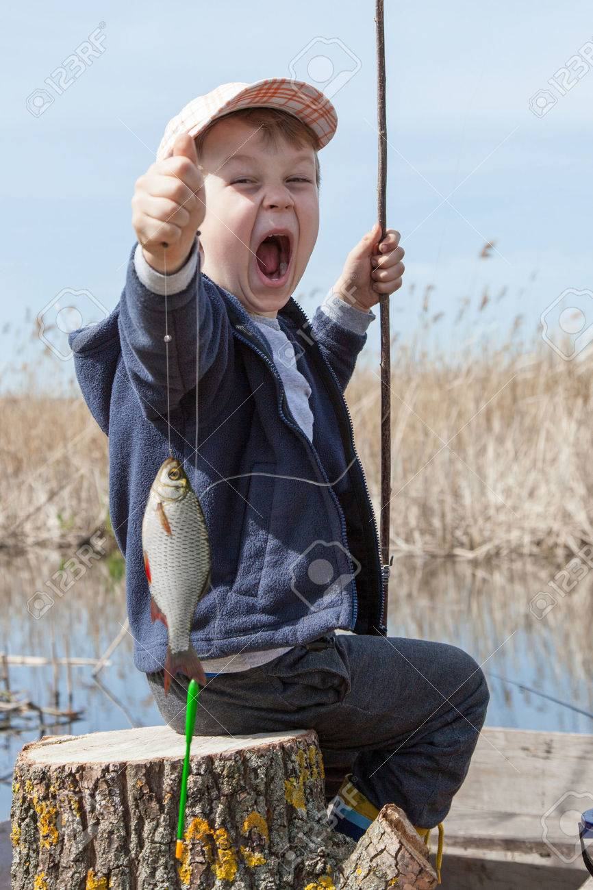 Happy boy holding a fish caught in the pond - 28062560