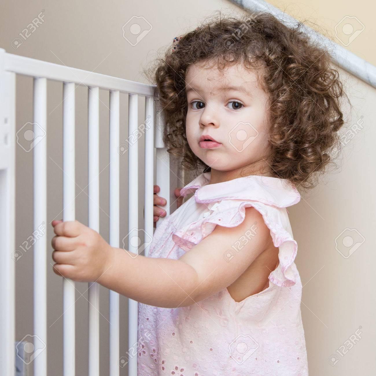 Portrait of a cute curly-hair girl near stair gate Standard-Bild - 34233649