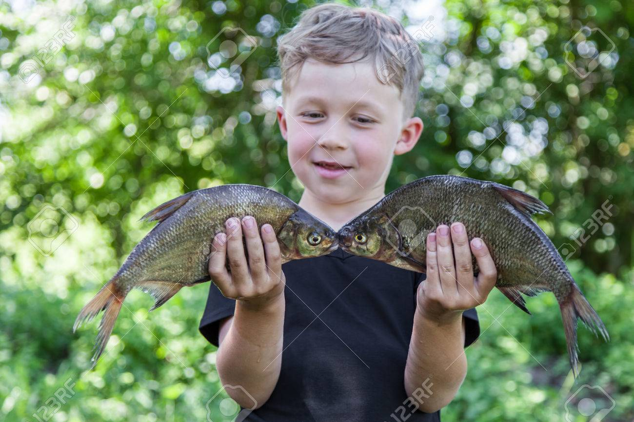 Happy boy fisherman holding two fish bream caught at the bait - 41068015