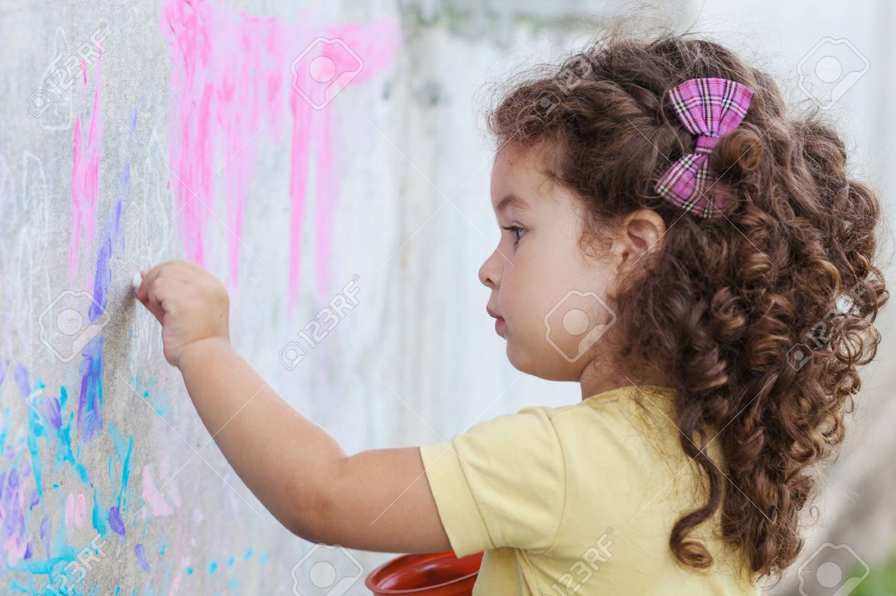 Curly cute baby girl drawing with chalk on the wall Standard-Bild - 44171820