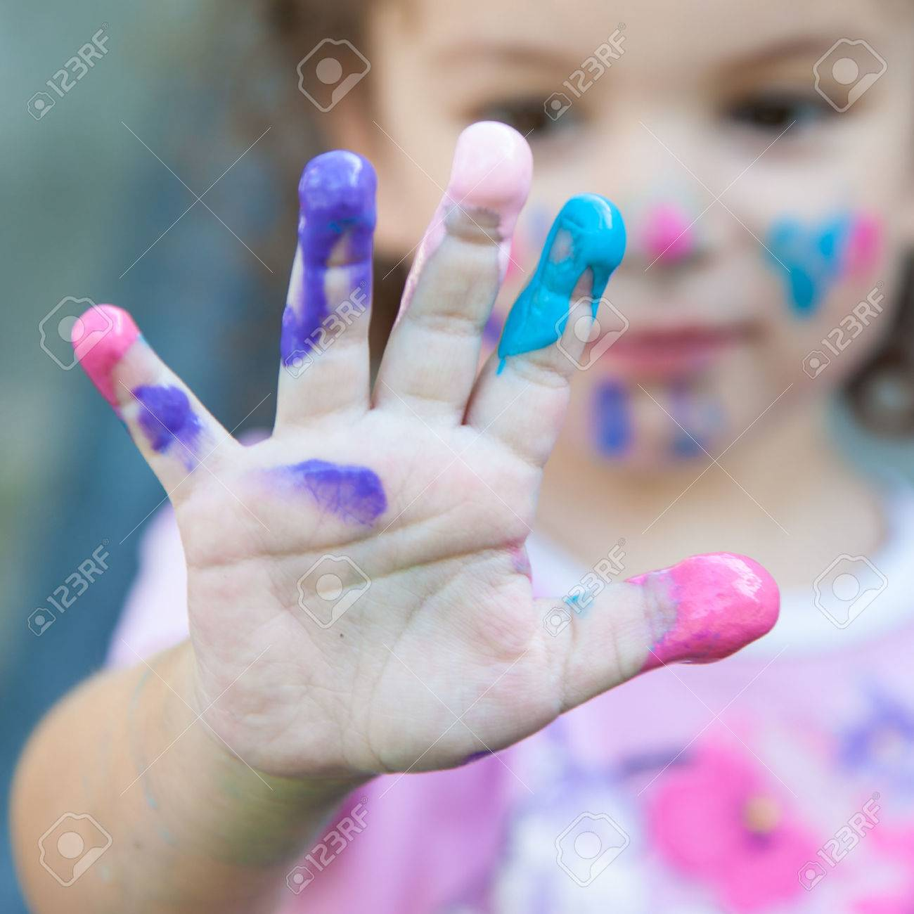 Baby girl is playing with paints outdoors Standard-Bild - 45934539