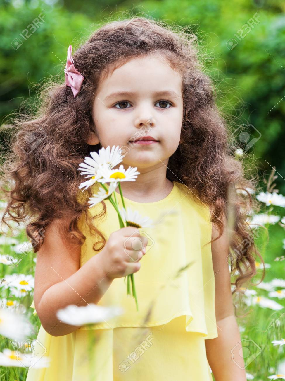 Cute baby girl with daisy flowers outdoors stock photo 99117315