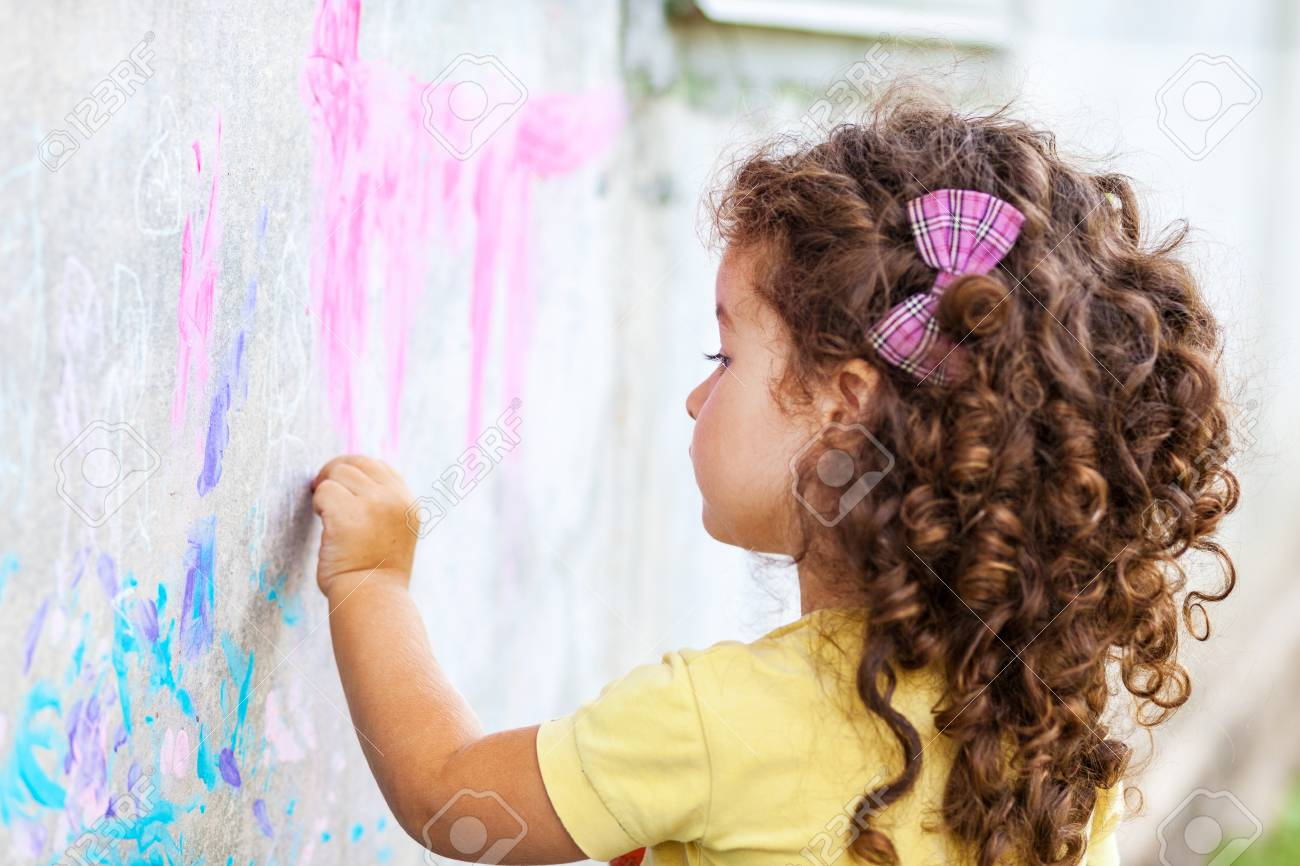 Curly cute baby girl drawing with chalk on the wall - 102313165
