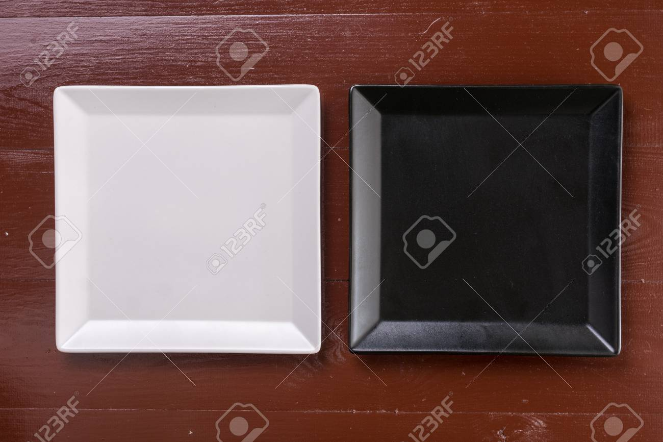 Flat lay above black and white square plates on the wooden boards table. Stock Photo & Flat Lay Above Black And White Square Plates On The Wooden Boards ...