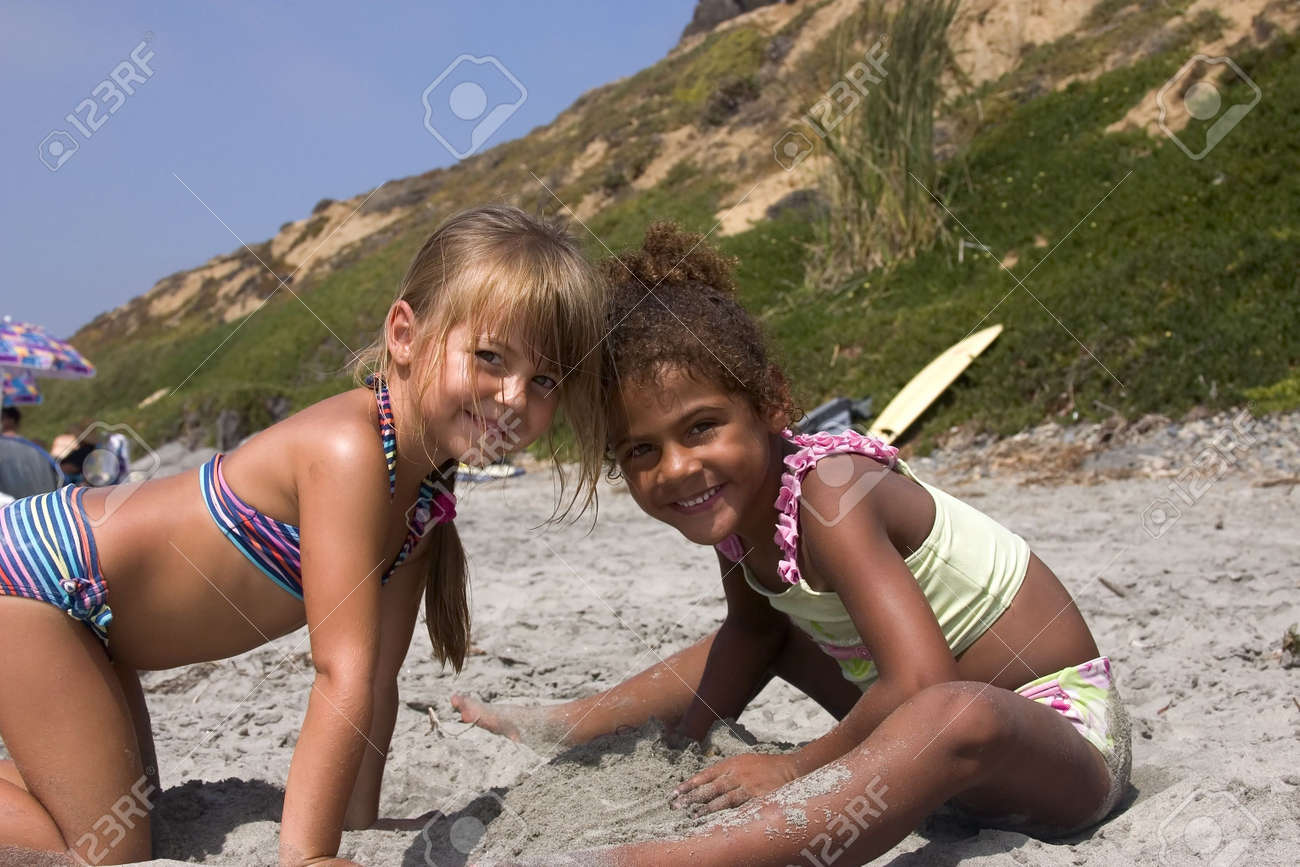 6c0c7a9a477fe two cute girls playing in the sand at the beach. Stock Photo - 245059