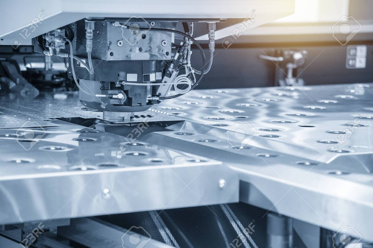 The hi-speed CNC punching machine in light blue scene. Modern metalworking manufacturing process by punching machine. - 124388940