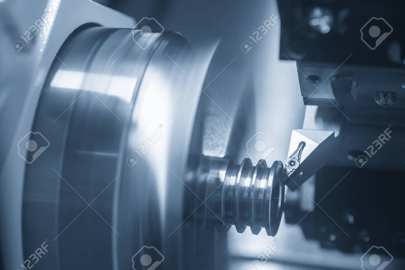 The CNC lathe machine cutting the slot at the metal parts. The automotive parts manufacturing process by turning machine . - 128806436