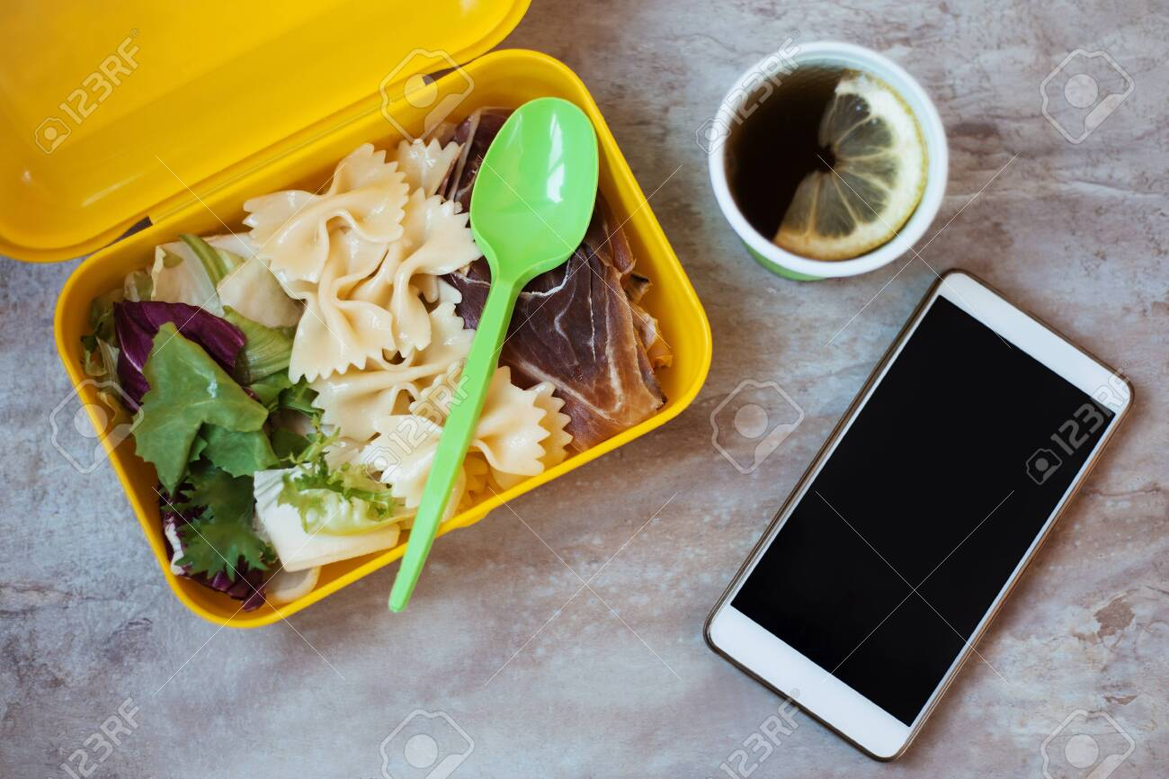 Lunch box with lunch, tea, spoon, phone  Lunch box with pasta,