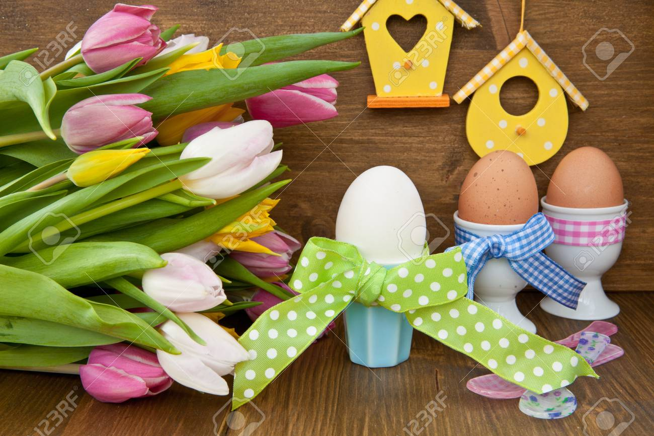 Fresh colorful tulips and boiled eggs in colorful cups for easter Stock Photo - 25276020