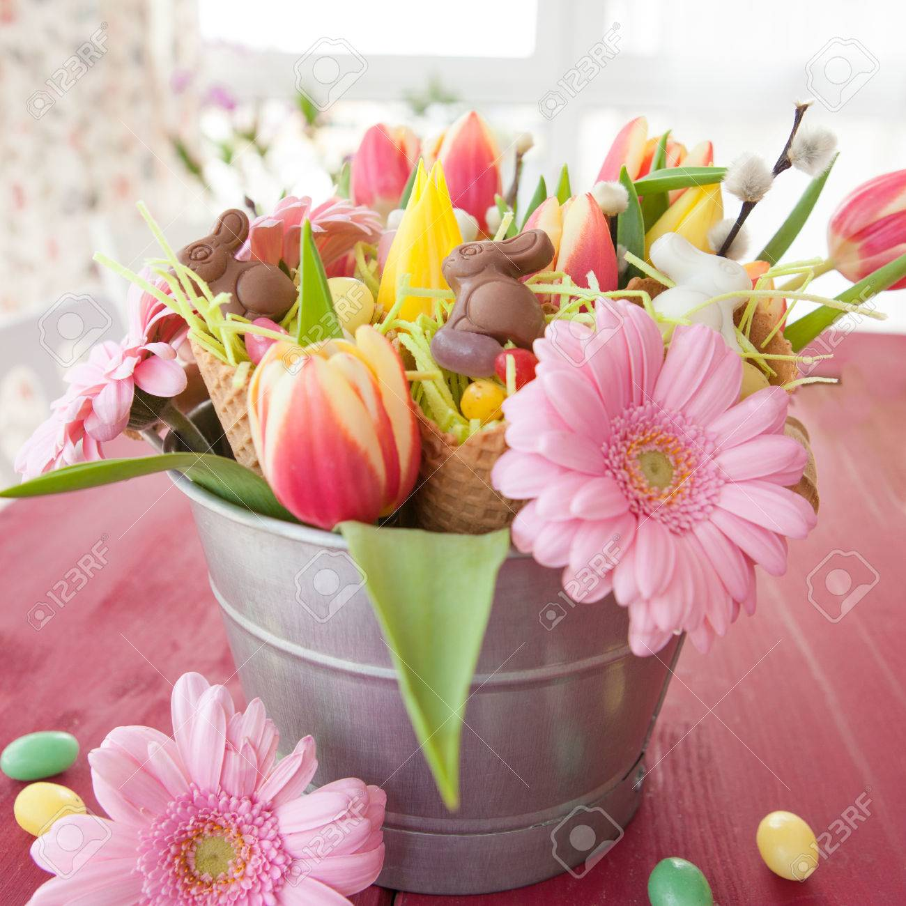 Colorful Spring Flowers With Fun Easter Candy And Chocolates Stock