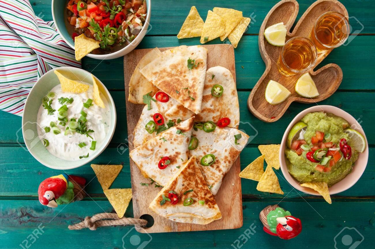 Delicious homemade quesadillas with fresh guacamole and tomato salsa - 121462111