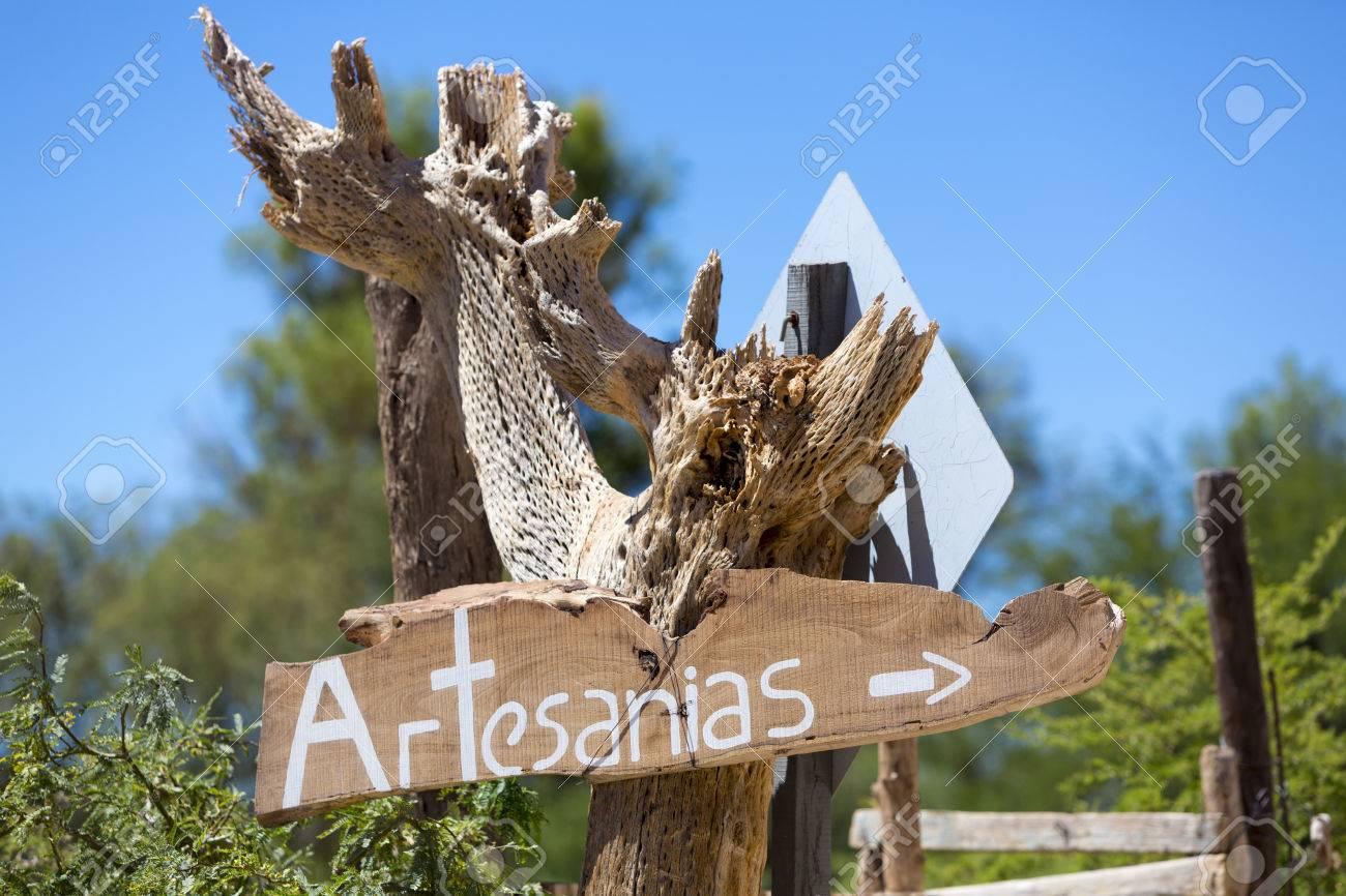 Cartel De Madera De Cactus Seca Con Artesanias Escritos En Español O Artesanal En Inglés Borrosa Azul Y Verde Fondo De La Naturaleza Cafayate