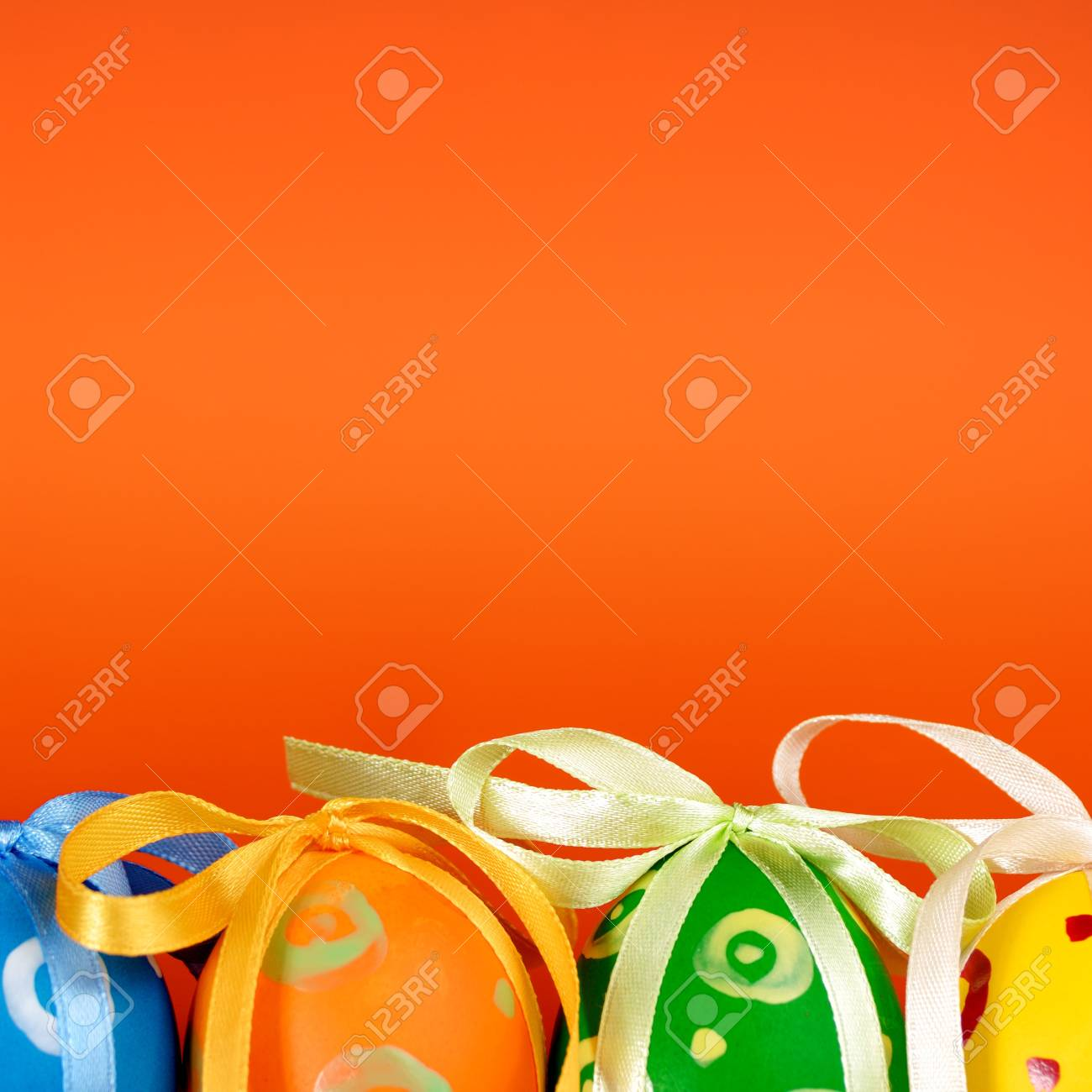 Easter eggs with bows over orange background Stock Photo - 8680878
