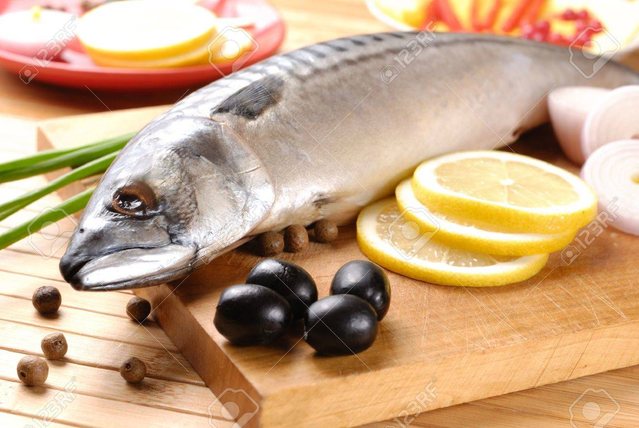 Fresh mackerel with olives, lemons and onions over wooden chopping board Stock Photo - 8681034