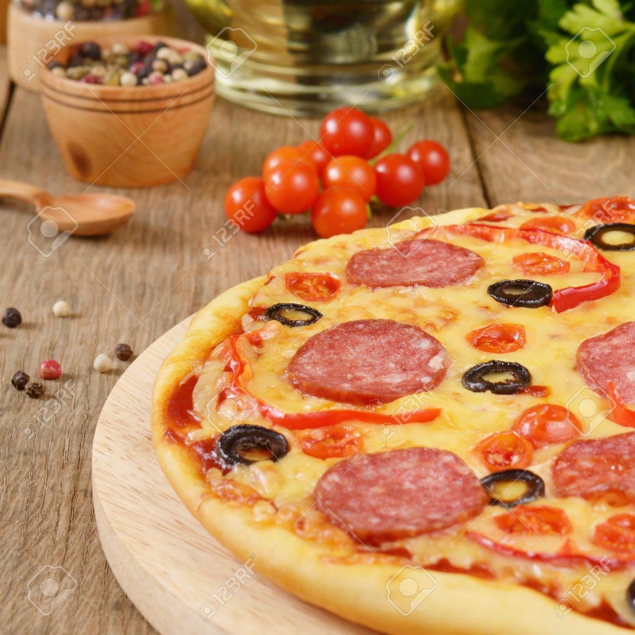 Pepperoni pizza with cherry and paprika on the kitchen table Stock Photo - 12896350