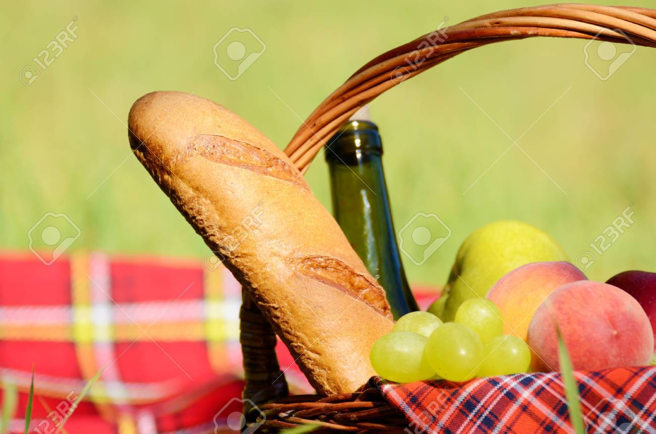 Picnic basket with red napkin fool of fruits, bread and wine on green grass Stock Photo - 14291739