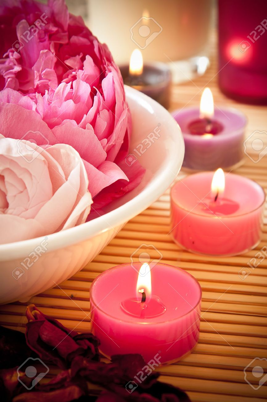 A bowl full of beautiful pink aromatherapy flowers with candles Spa scene - 13897267