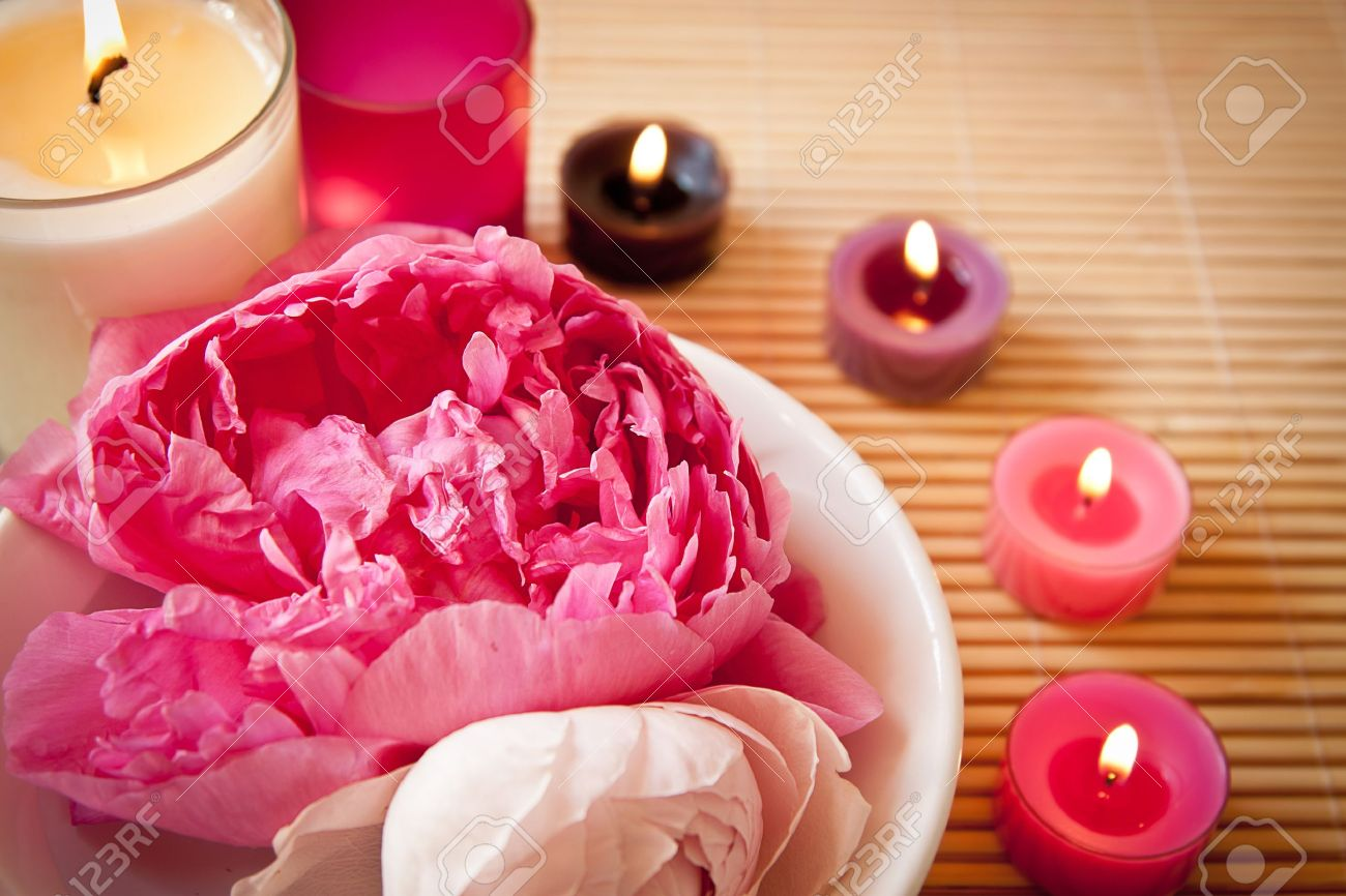 A bowl full of beautiful pink aromatherapy flowers with candles  Spa scene  Landscape orientation, focus on the flowers Stock Photo - 13897395