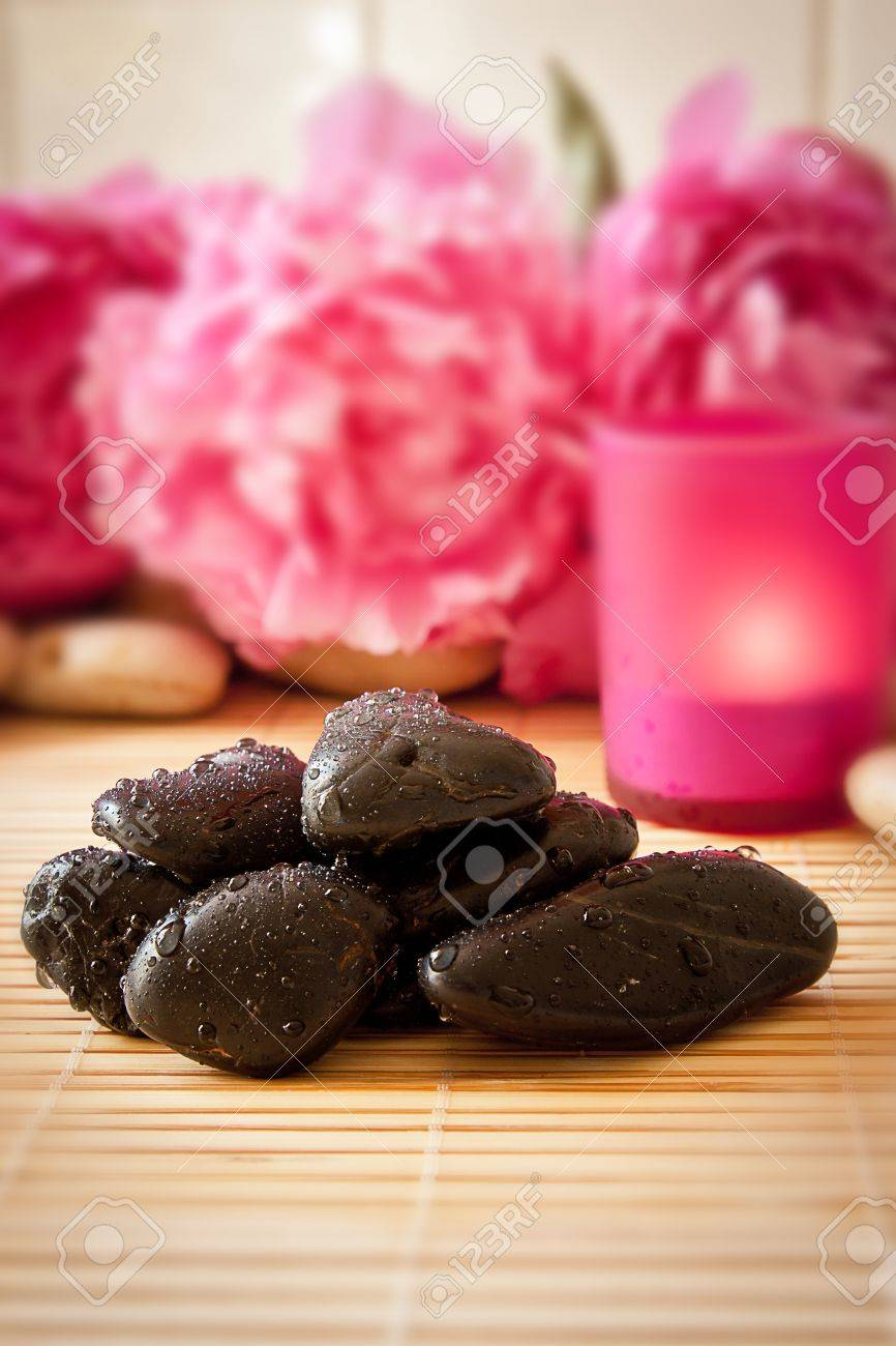 Black massage pebbles on a bamboo mat with flowers and candles in the background  Spa scene Stock Photo - 13896954