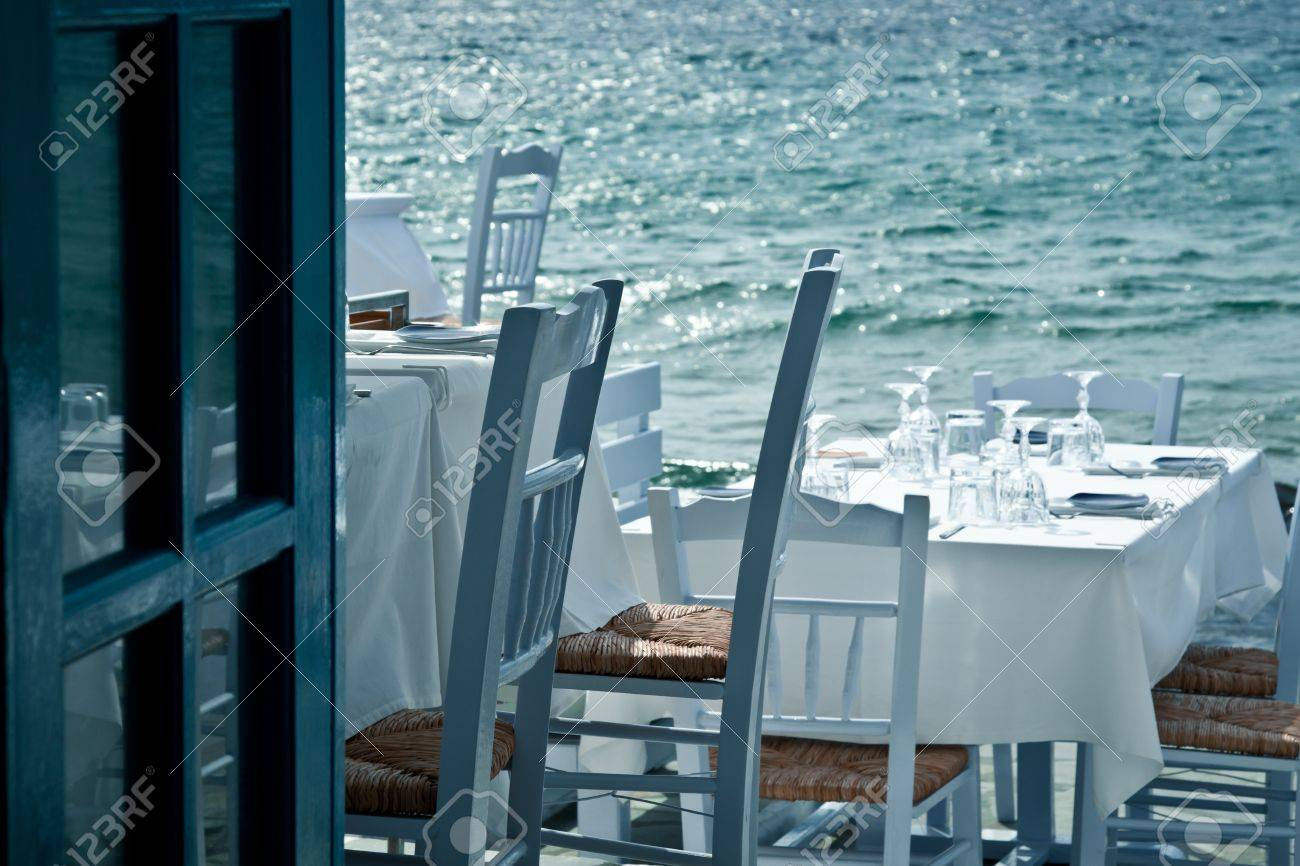 Restaurant tables on the sea in a Greek village - 13897480
