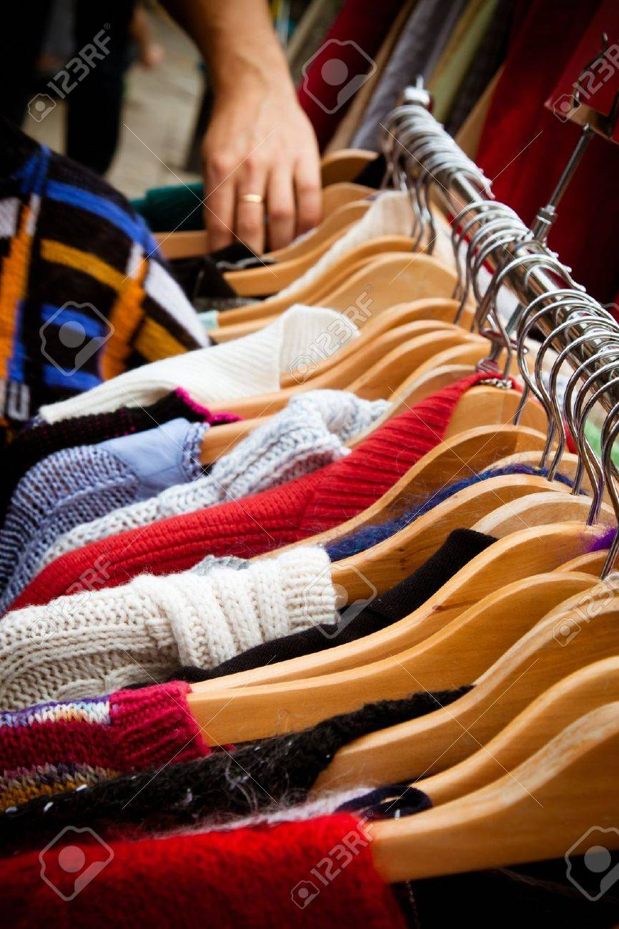 A rack of second-hand jumpers and cardigans at a market in London recession bargains Hand of someone browsing visible in the background - 13899114