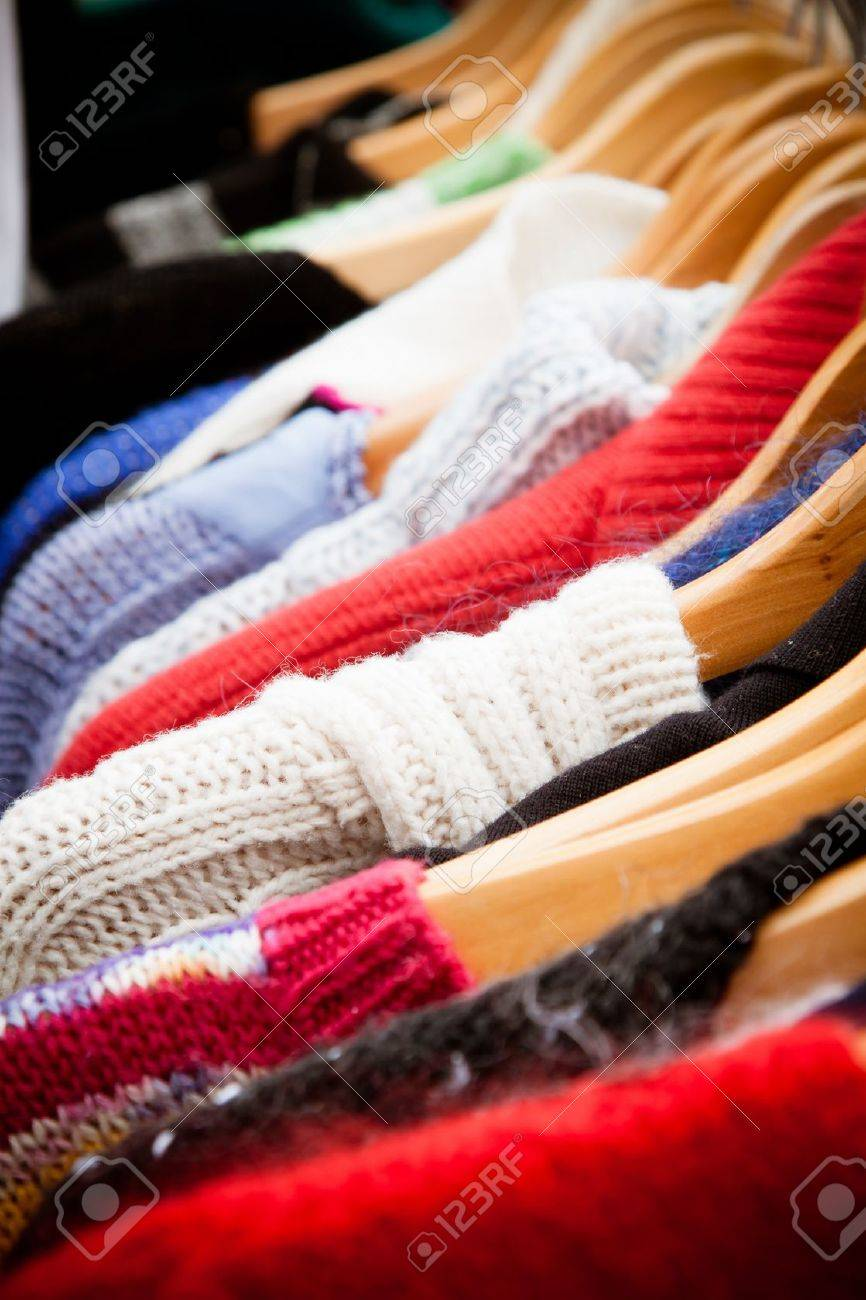 Close-up on a rack of second-hand jumpers and cardigans at a market in London recession bargains - 13899087