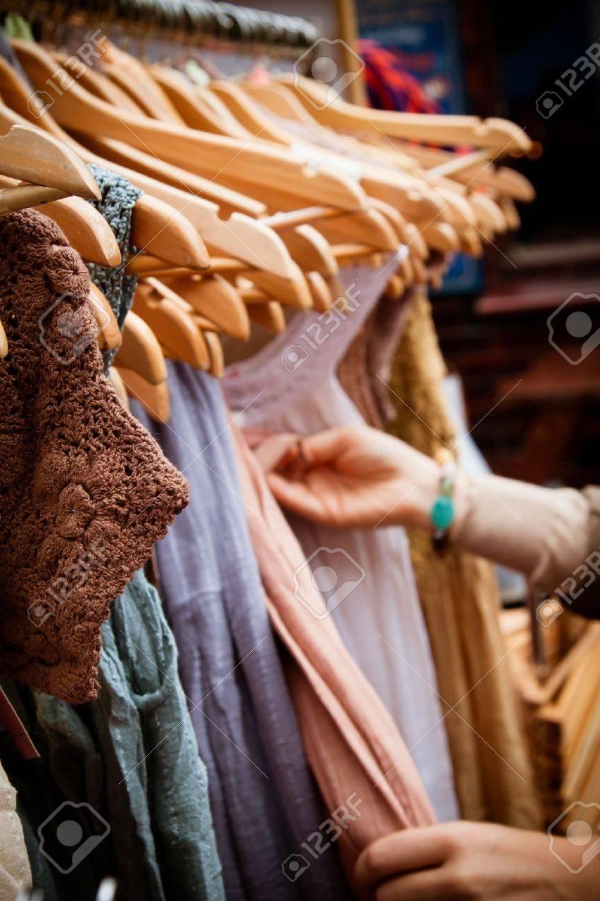 Recession bargains: rack of second-hand dresses for sale at market. Portrait orientation. - 20013135
