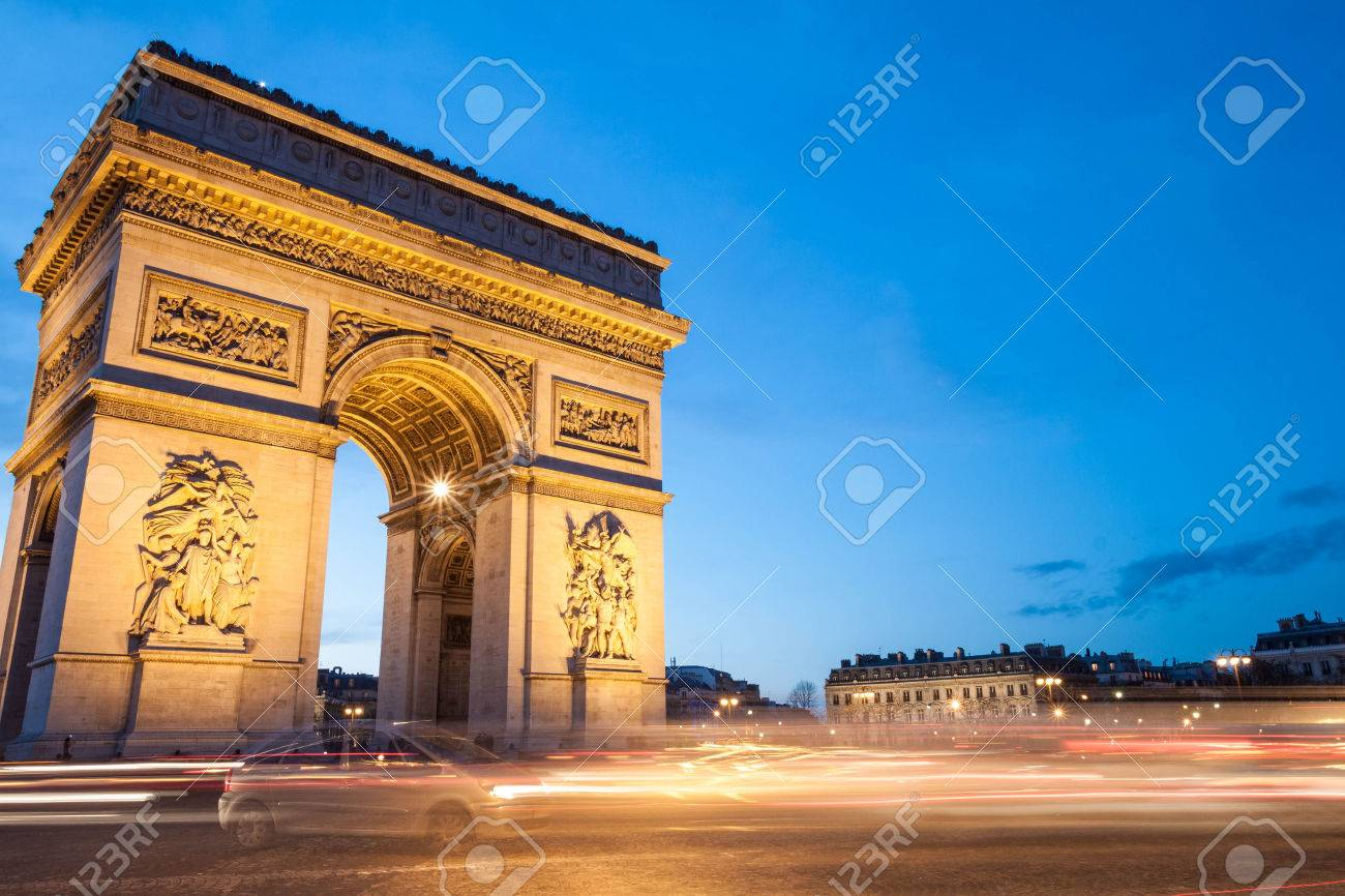 The Arc de Triomphe in Paris, France, at twilight with traffic light trails. - 25991156