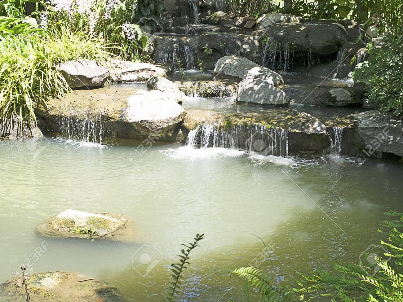 Un petit jardin de cascade artificielle, les rochers et petit étang.