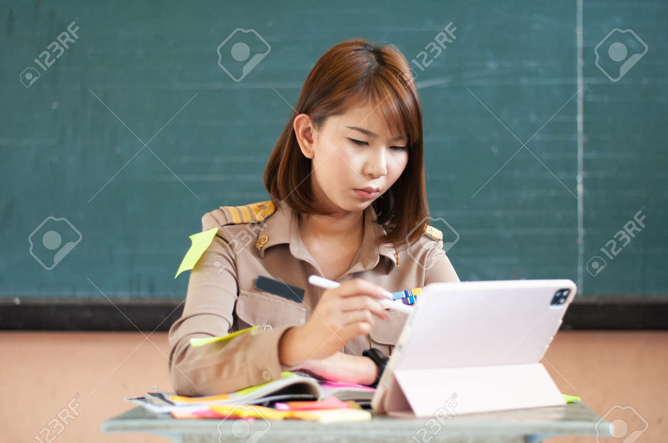 Female Thai teacher holding notebook to the computer while smiling - 166602849