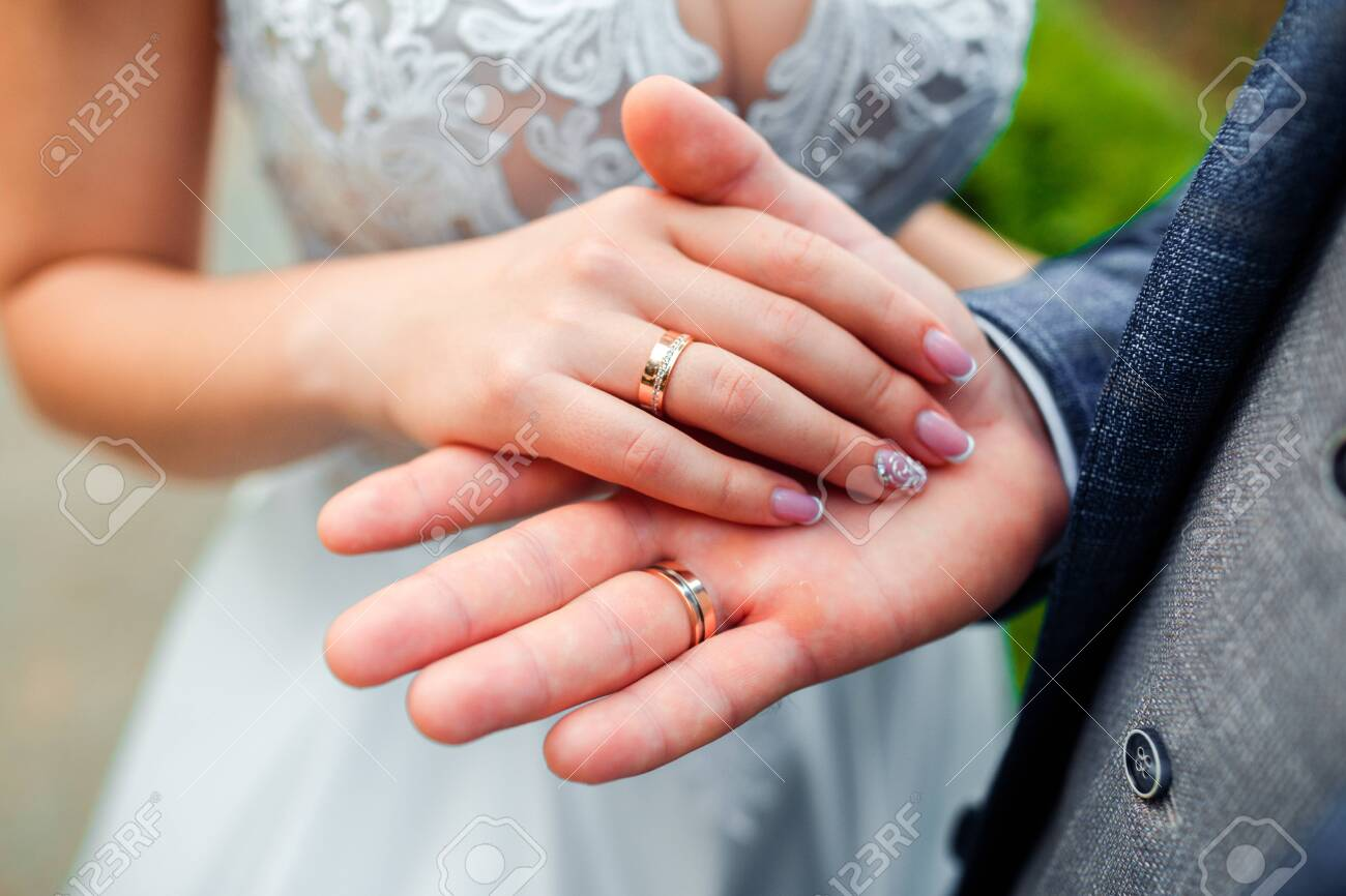 Wedding rings in the hands of the bride and groom. - 130020505