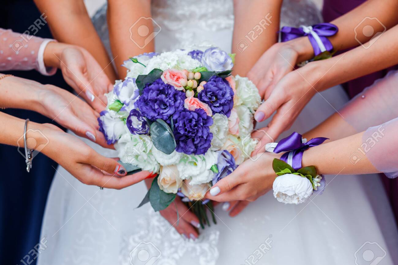 Wedding bouquet in the hands of the bride. Many hands of girl. - 142274614