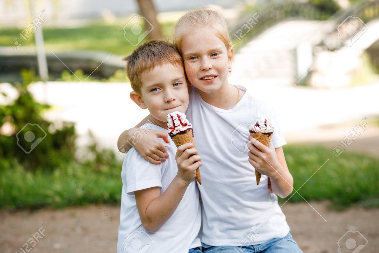 Children eat ice cream in the park. - 168634123