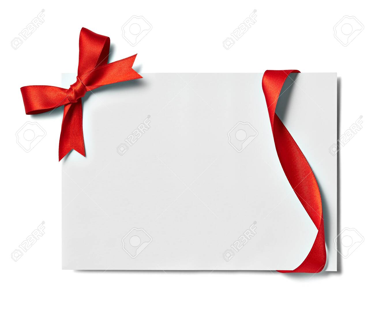 close up of a note card with red ribbon bow on white background - 134101877