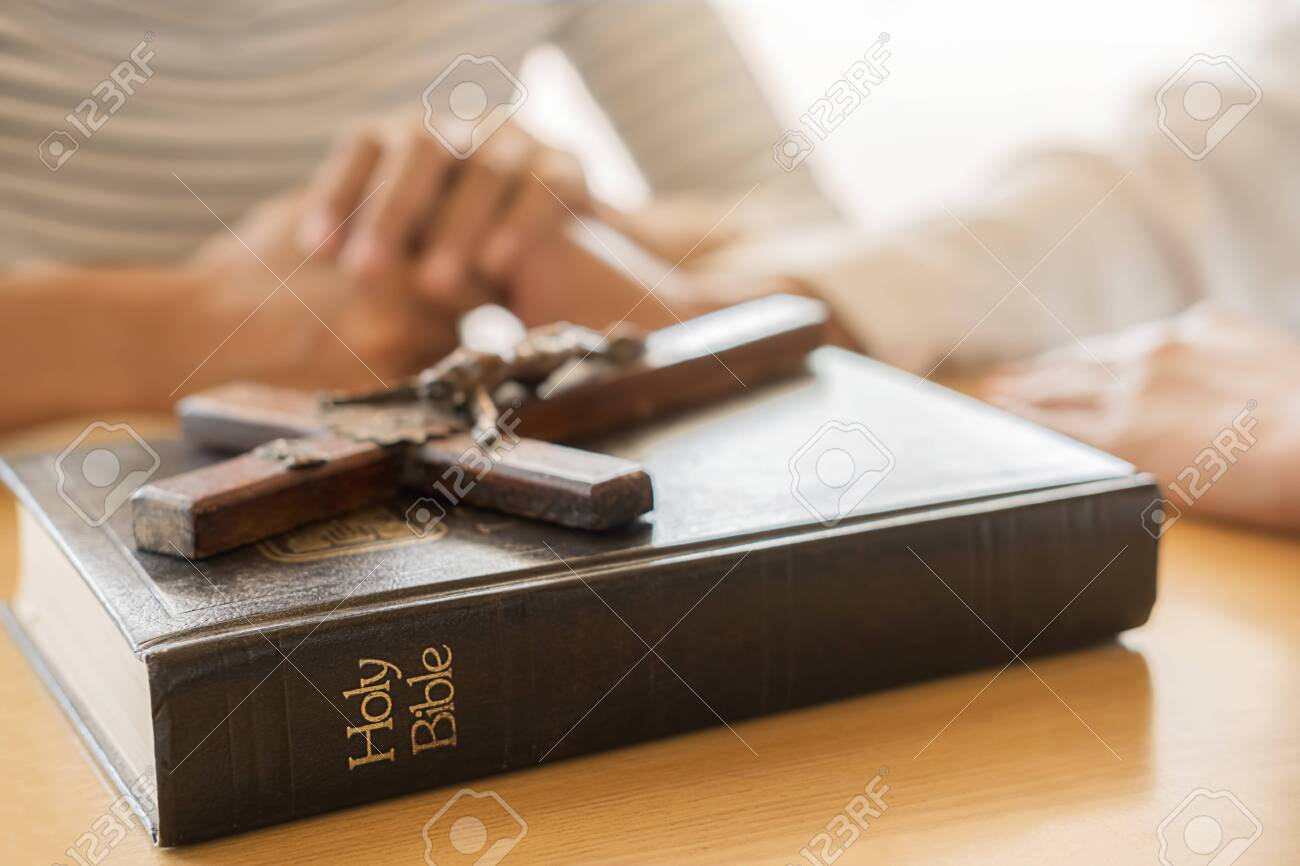 Christian woman praying with hands together on holy bible and wooden cross. Woman pray for god blessing to wishing have a better life and believe in goodness. - 136660527