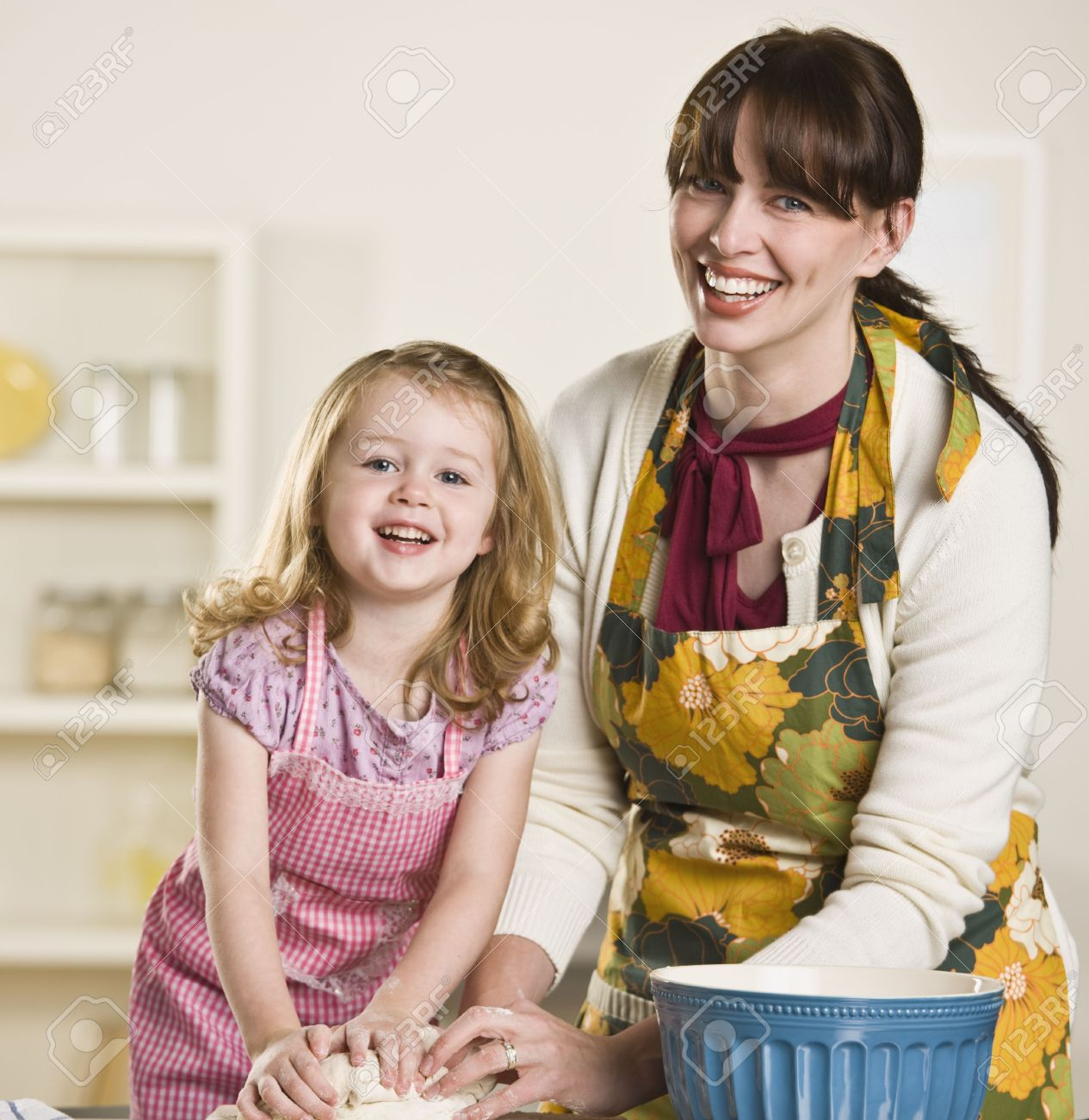 Brunette Mom And Blond Daughter Making Bread On The Kitchen Counter While Wearing Aprons