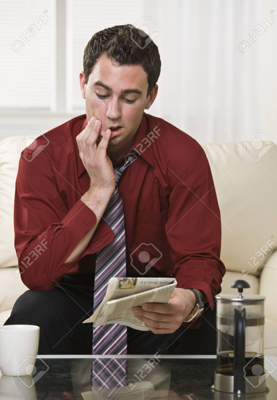 Attractive male reading the paper with a concerned and focused look on his face. Drinking coffee, looking at the paper. vertical. Stock Photo - 5047122