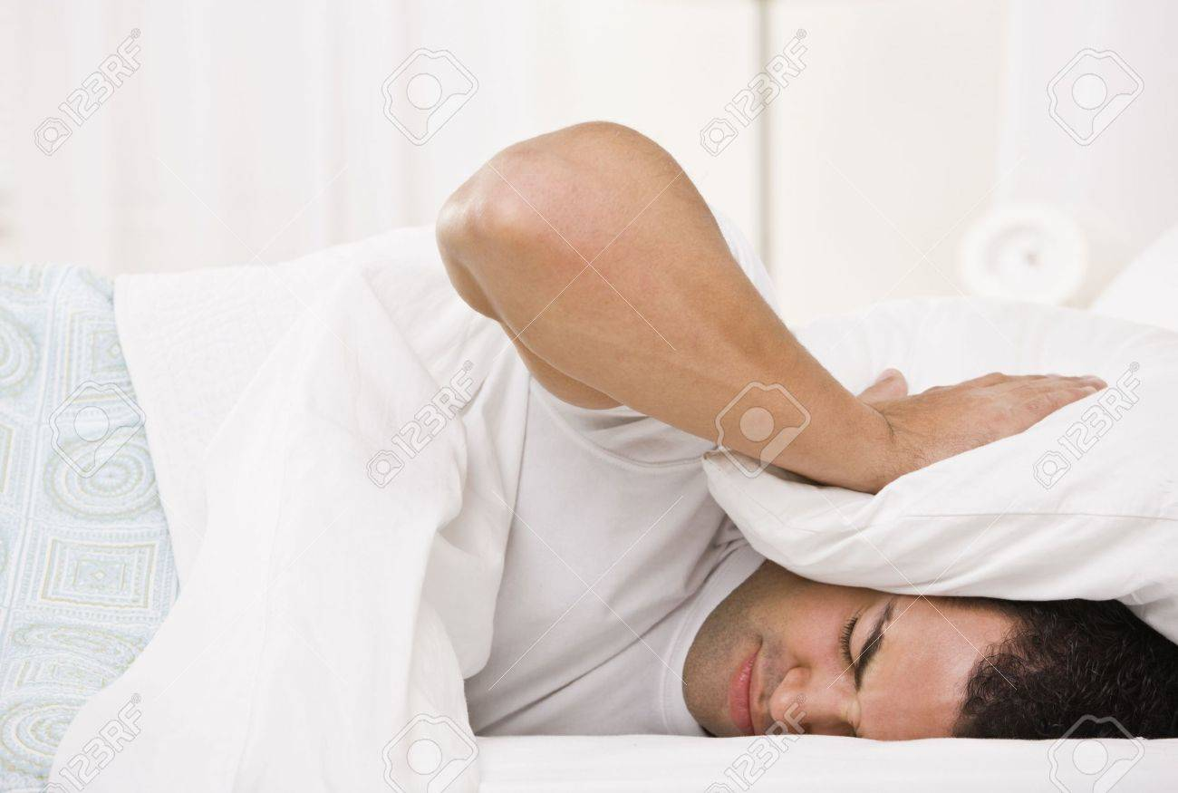 Head On Pillow: A Tired Looking Man Holding A Pillow Over His Head And Lying