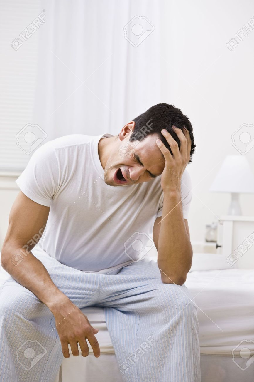 efa75f12bb7 A Man Yawning. He Is Sitting On The Edge Of A Bed. Vertically ...