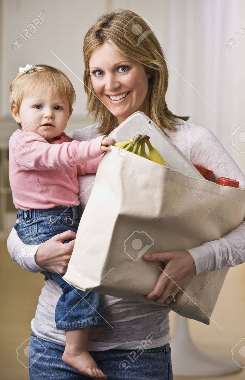 A young mother is holding her daughter in one arm and a bag of groceries in the other.  She is smiling at the camera.  Vertically framed shot. Stock Photo - 5333556