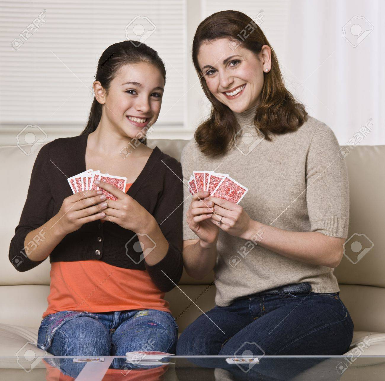 A young mother and her daughter are playing cards together.  They are smiling at the camera.  Square framed shot. Stock Photo - 5334028