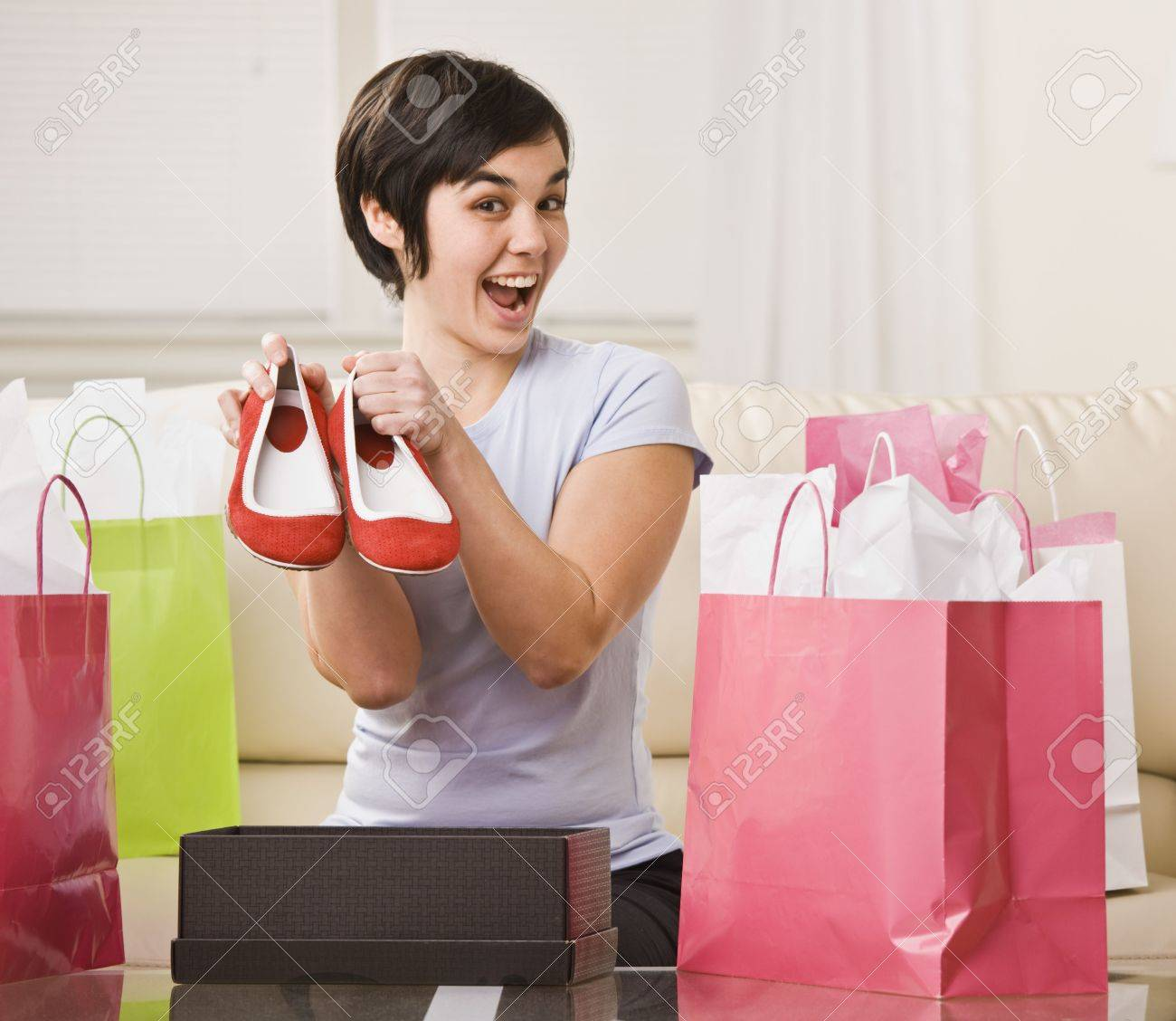 A young woman is surrounded by shopping bags and is holding out a pair of shoes.  She is smiling at the camera.  Square framed shot. Stock Photo - 5333259