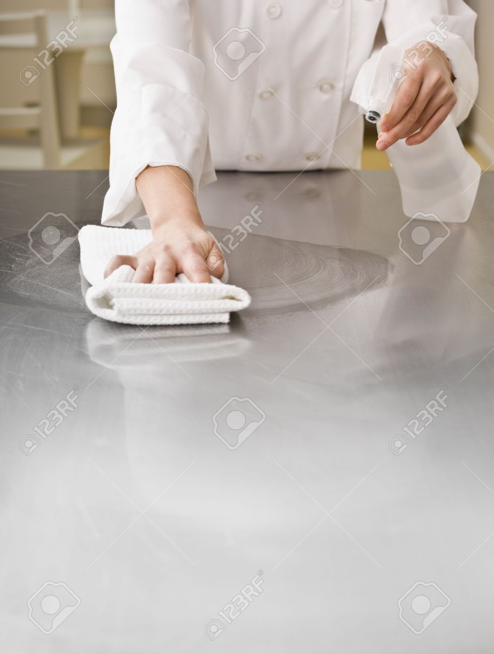 A chef is cleaning a counter in a professional kitchen with a bottle of solution and a rag. Vertically framed shot. - 5333254