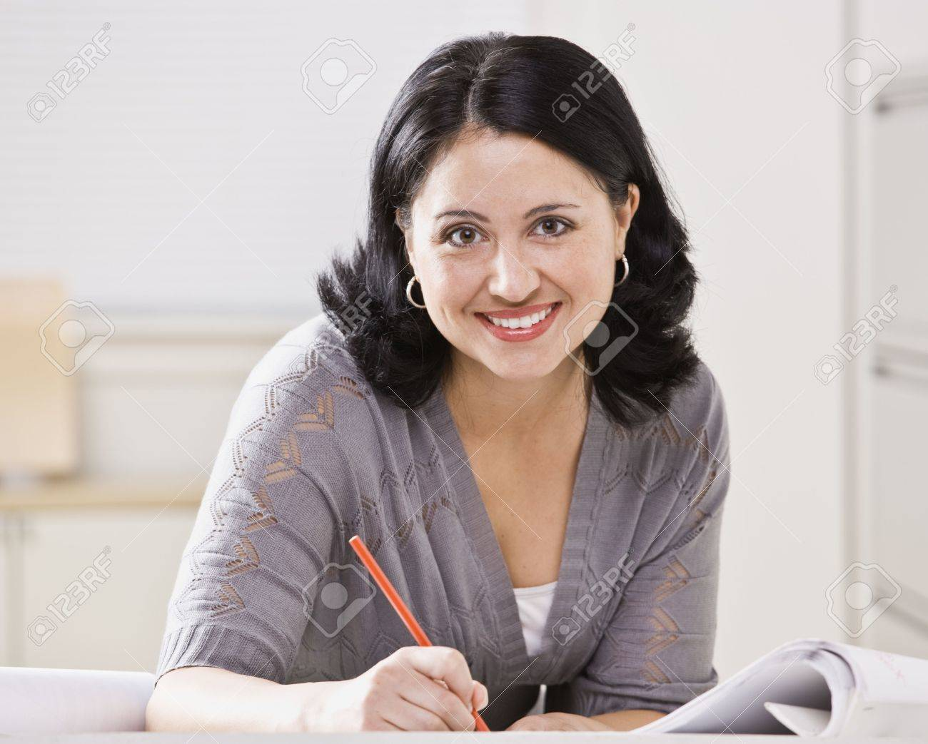 A beautiful Hispanic woman writing at a desk.  She is smiling at the camera.  Square compostion. Stock Photo - 5333704