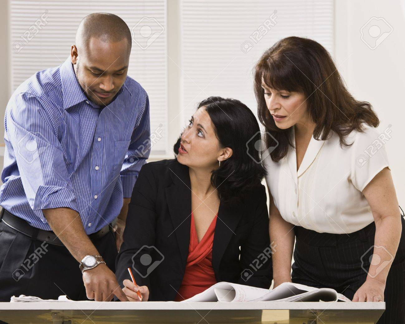 A group of business people are in an office and are looking at some paperwork.  They are talking and looking away from the camera.  Horizontally framed shot. Stock Photo - 5334046