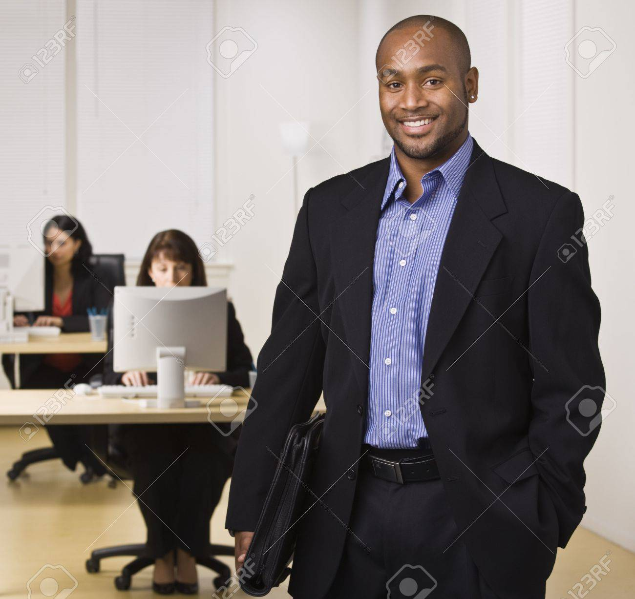 A young businessman is standing in an office with some other business people.  He is smiling at the camera.  Horizontally framed shot. Stock Photo - 5333162