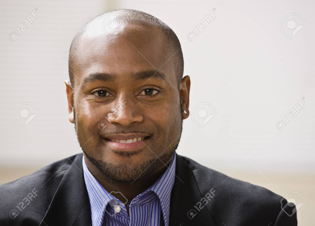 A young businessman is smiling at the camera.  Horizontally framed shot. Stock Photo - 5333855