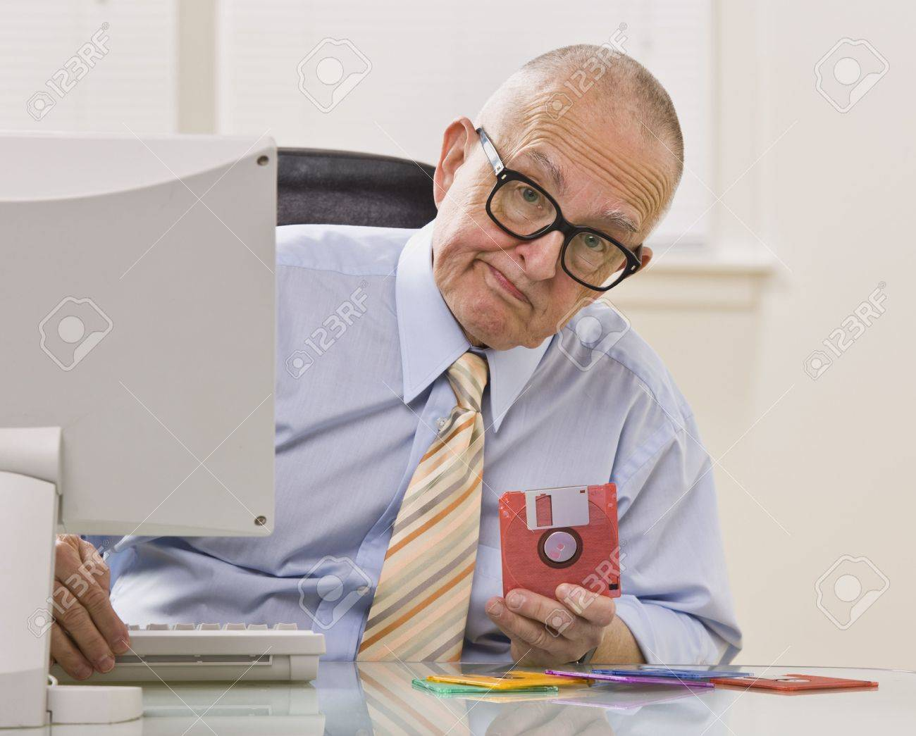 floppy office. an elderly businessman is seated in office holding a floppy disk he looking