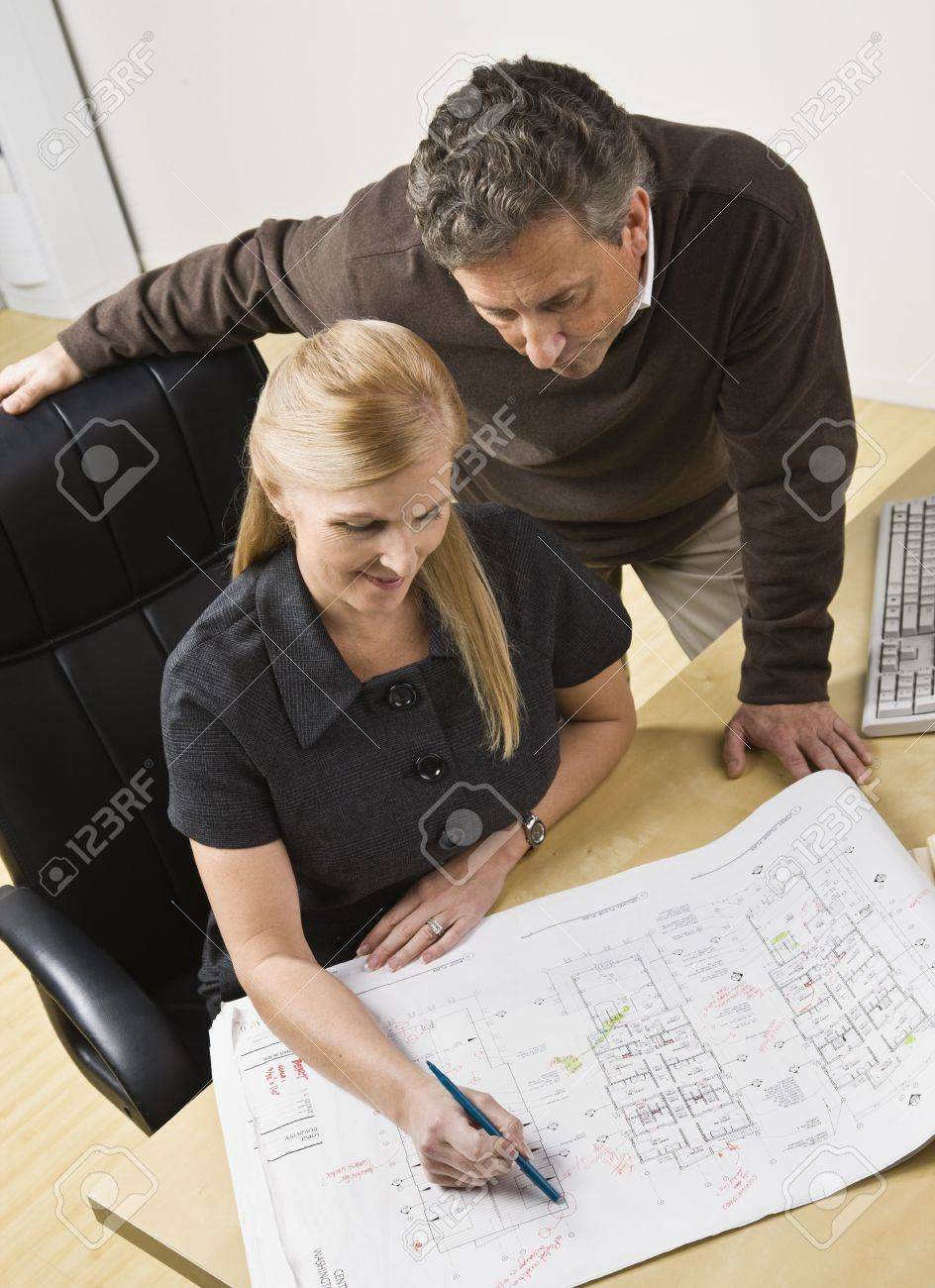 Two architects, male standing over female, looking at the drawing on the desk. Vertical Stock Photo - 5333741